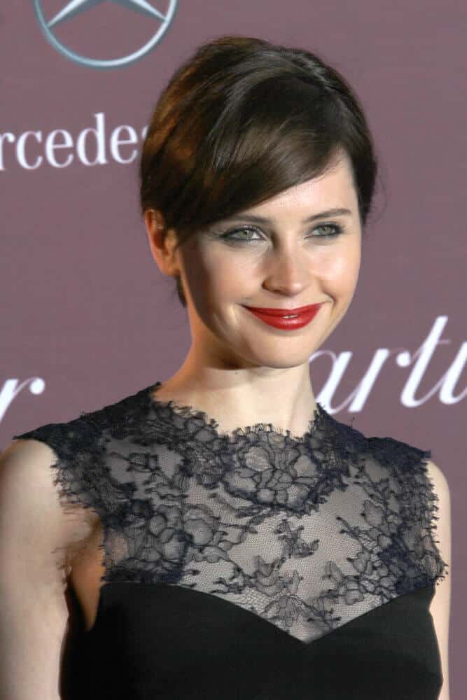 During the 2015 Palm Springs Film Festival Awards Gala, Felicity Jones attended the in this nicely-done low bun with side-swept bangs.