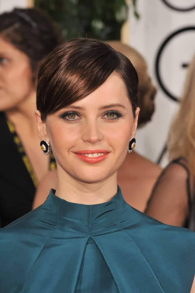 Felicity Jones in a neat and classy upstyle with side-swept bangs.