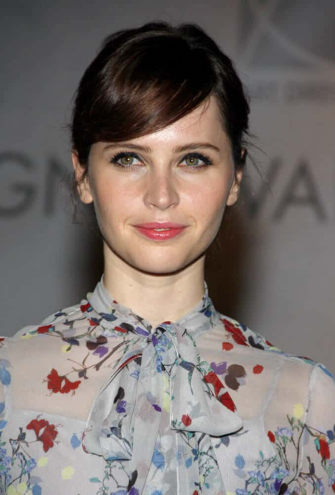 Felicity Jones oozing with elegance and femininity with her low bun hairstyle with side bangs.