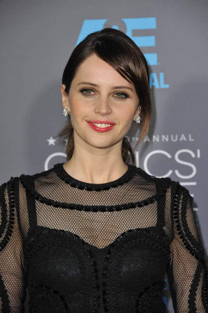 Felicity Jones sporting a low ponytail with a thick, side tendrils.
