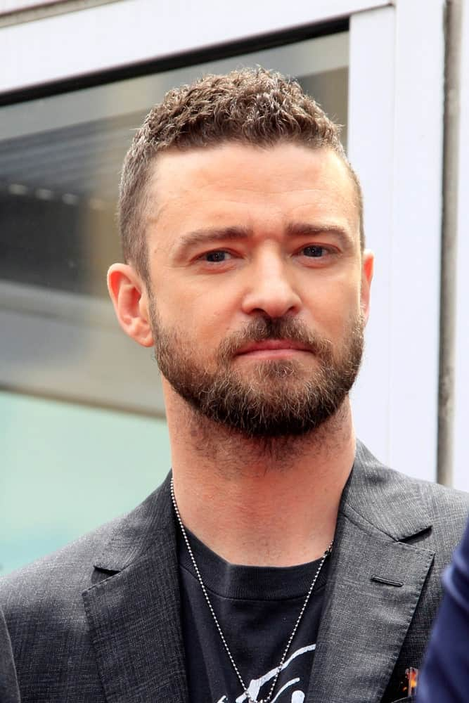 Justin Timberlake was at the *NSYNC Star Ceremony on the Hollywood Walk of Fame on April 30, 2018 in Los Angeles, CA. He went with an edgy short curl look to match his thick beard and rocker chic outfit.