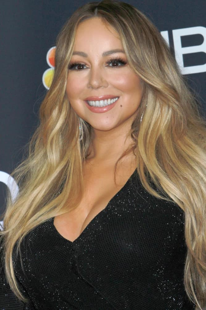 Mariah Carey attended the 2019 Billboard Music Awards at MGM Grand Garden Arena on May 1, 2019 in Las Vegas, NV wearing a sleek glittery black dress that makes the light tone of her long wavy ombre highlights.