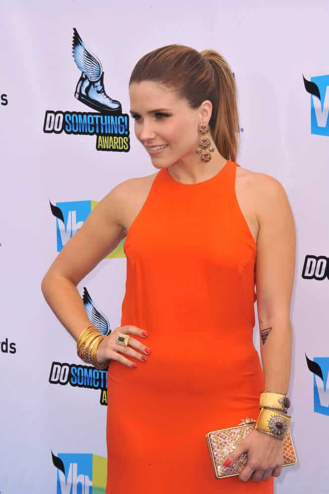 The actress Sophia Bush with straight hair in dark copper tones, styled into a neat ponytail is seen at the 2012 Do Something Awards.
