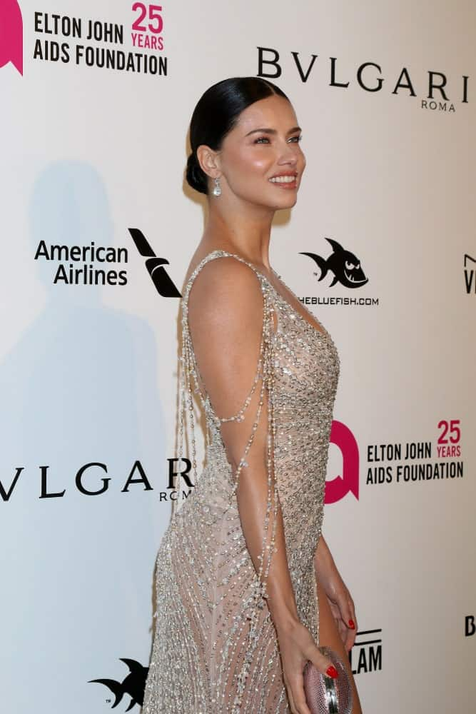 Adriana Lima was at the 2018 Elton John AIDS Foundation Oscar Viewing Party at the West Hollywood Park on March 4, 2018 in West Hollywood wearing a sheer jazzy dress that is paired with a sophisticated low bun hairstyle.