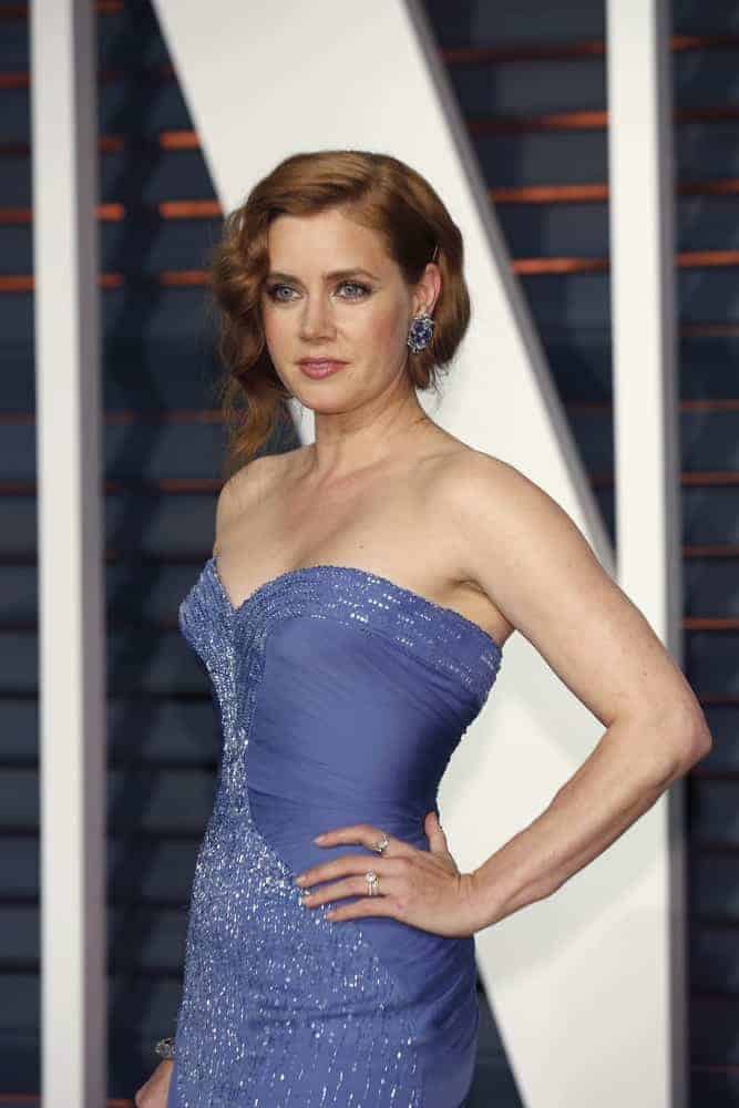 Amy Adams attended the Vanity Fair Oscar Party 2015 at the Wallis Annenberg Center for the Performing Arts on February 22, 2015, in Beverly Hills, CA. She wore a stunning strapless dress with her loose bun hairstyle with wavy side-swept bangs.