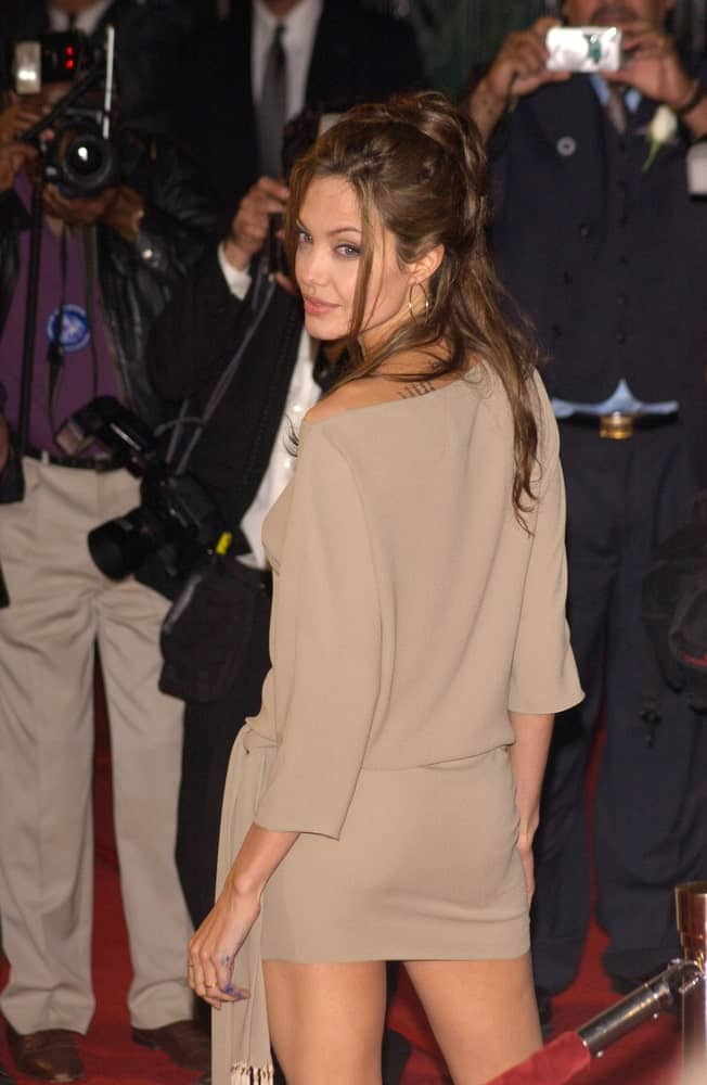 Actress Angelina Jolie was at the world premiere, in Hollywood, of her new movie Taking Lives on March 16, 2004. She wore a stunning brown short dress that she paired with a messy and loose half-up hairstyle with tendrils and bangs.