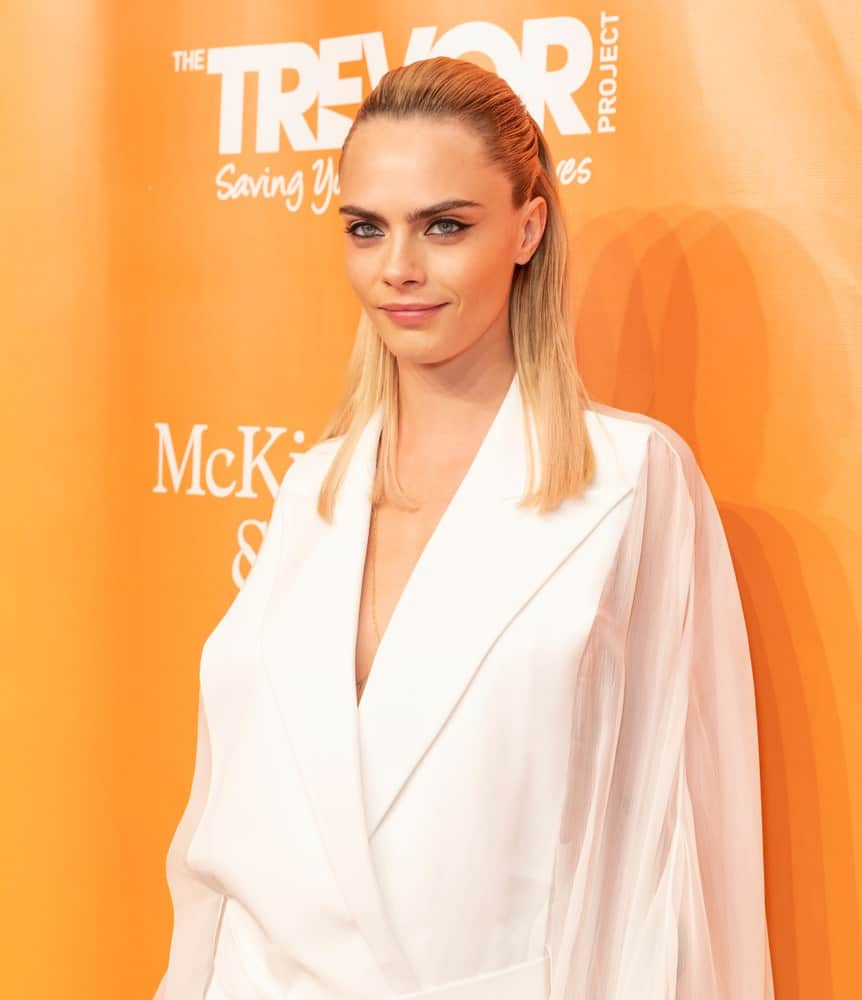 On June 17, 2019, Cara Delevingne attended the 2019 TrevorLIVE New York Gala for The Trevor Project at Cipriani Wall Street. She was quite lovely in the white outfit that she paired with a slick half-up hairstyle with a sandy blond tone.