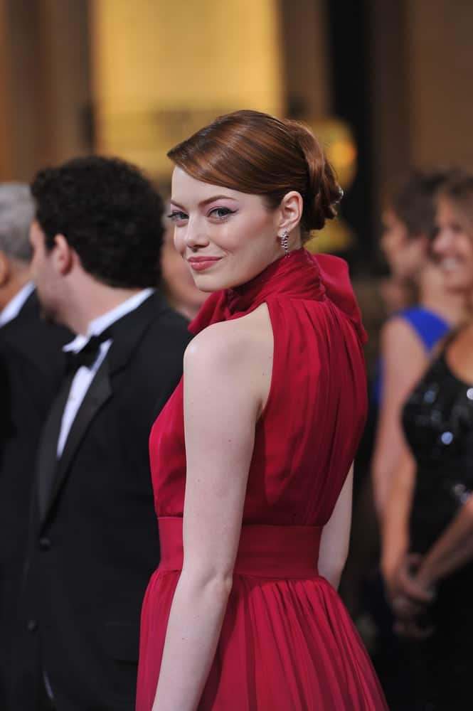 Emma Stone's highlighted red hair was styled into this elegant upstyle with side-swept bangs to match her lovely red dress at the 84th Annual Academy Awards at the Hollywood & Highland Theatre, Hollywood on February 26, 2012, in Los Angeles, CA.