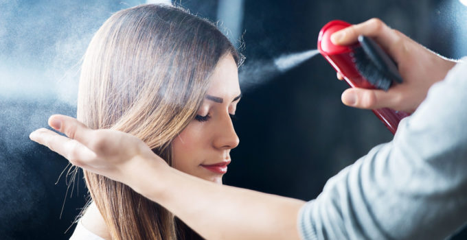 Hairdresser applying hair spray to woman's hair