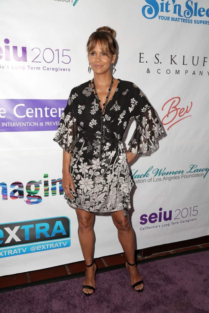 Halle Berry flaunted her legs with a short floral casual dress that she paired with her high bun hairstyle incorporated with highlighted wispy bangs at the 2018 Imagine Cocktail Party To Benefit Jenesse Center at the Wilshire Country Club on June 27, 2018, in Los Angeles.