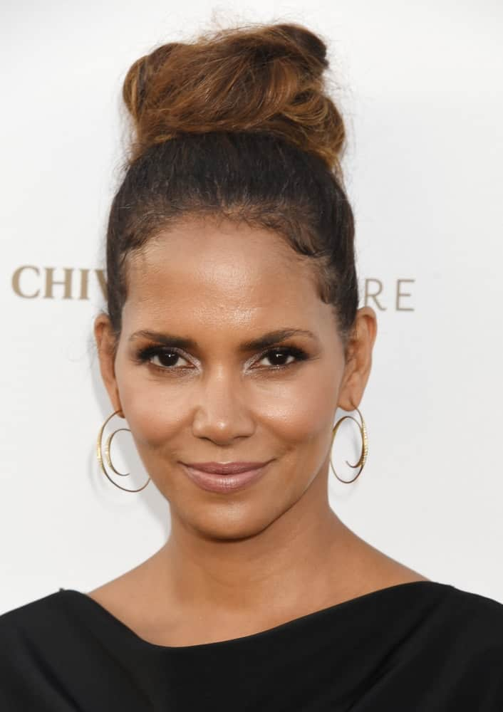 "Halle Berry emphasized her sexy neckline with a black dress that she paired with her top knot high bun hairstyle when she arrived at ""The Final Pitch"" from Chivas' The Venture on July 13, 2017, in Los Angeles, CA."