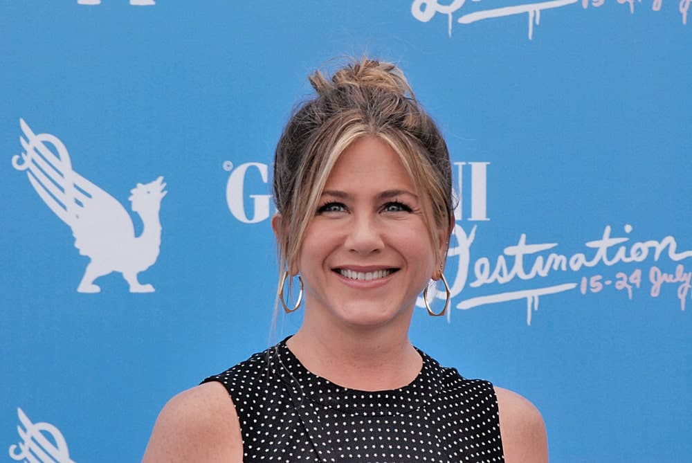 Jennifer Aniston showcased a messy bun hairstyle with curtain bangs at Giffoni Film Festival 2016 held on July 23rd. Gold hoop earrings and a black dotted dress completed the gorgeous look.
