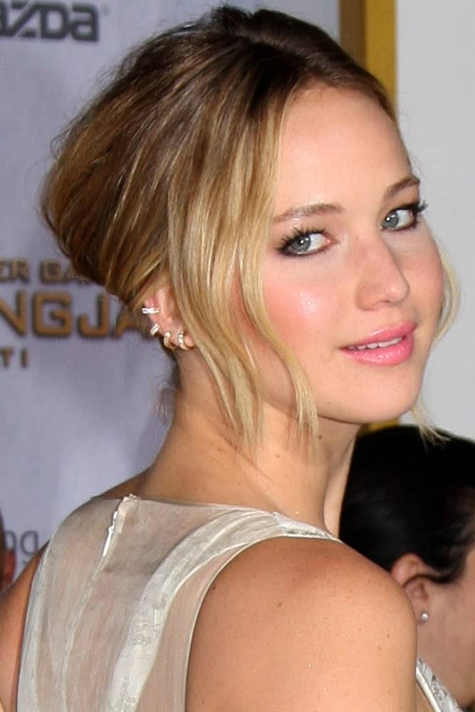 Jennifer Lawrence's white dress complimented her elegant messy half up with loose strands of bangs at the side at The Hunger Games: Mockingjay Part 1 Premiere at the Nokia Theater on November 17, 2014, in Los Angeles, CA.