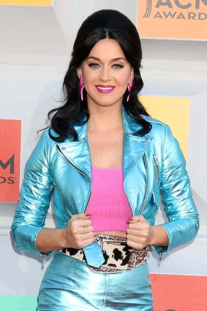Katy Perry is having fun wearing her metallic blue jacket paired with a high-waisted skirt and pink halter that goes well with her retro-inspired half up half down wavy hairstyle as she attends the 51st Academy of Country Music Awards.