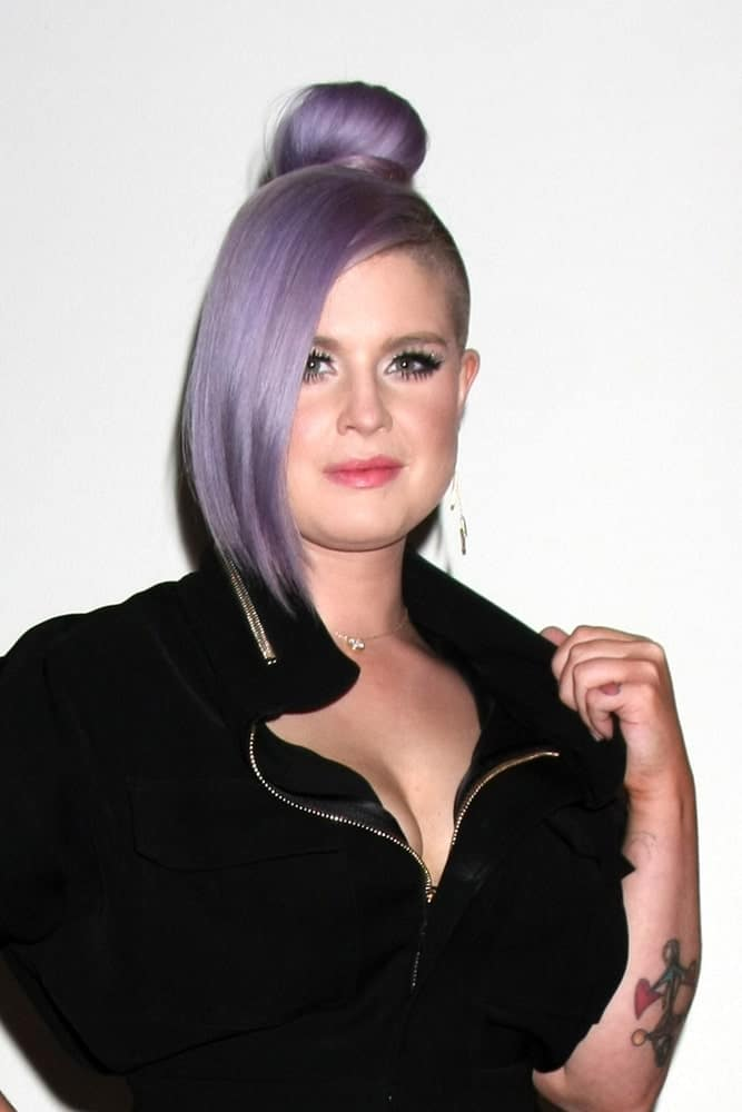 Kelly Osbourne shows off a purple bun hairstyle with long bangs swept to the right side. This was taken on October 12, 2015 during the Cosmopolitan Magazine's 50th Anniversary Party.