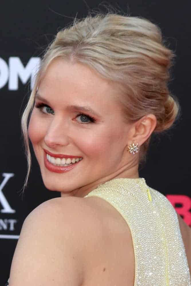 "Kristen Bell styled her blonde locks in a messy bun with a side tendril during the ""Bad Moms"" Los Angeles Premiere at the Village Theater on July 26, 2016"