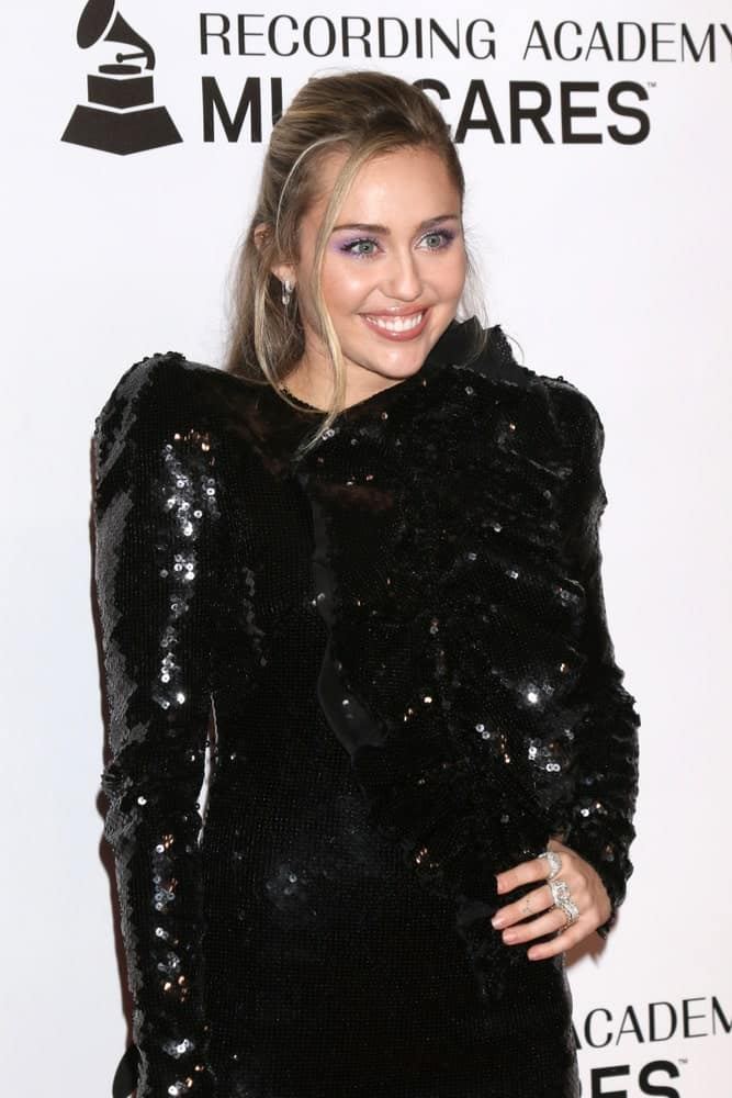 Miley Cyrus shone the brightest with her black shiny sequined dress and gorgeous half-up hairstyle with tendrils on the side at the MusiCares Person of the Year Gala at the LA Convention Center on February 8, 2019 in Los Angeles, CA.