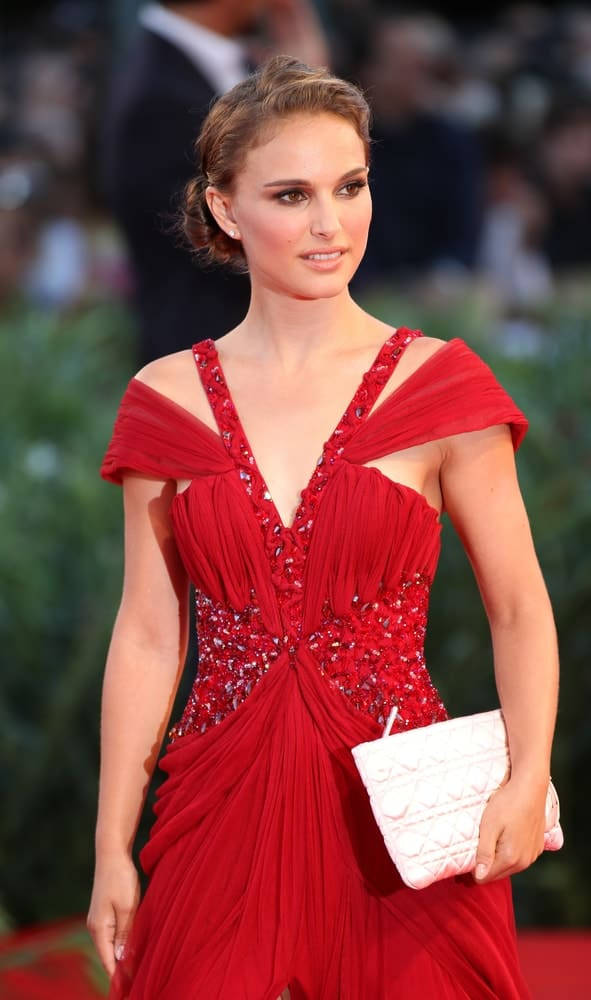 Actress Natalie Portman paired her elegant red dress with a messy and tousled low bun hairstyle when she attended the 'Black Swan' premiere during the 67th Venice Film Festival on September 1, 2010, in Venice, Italy.