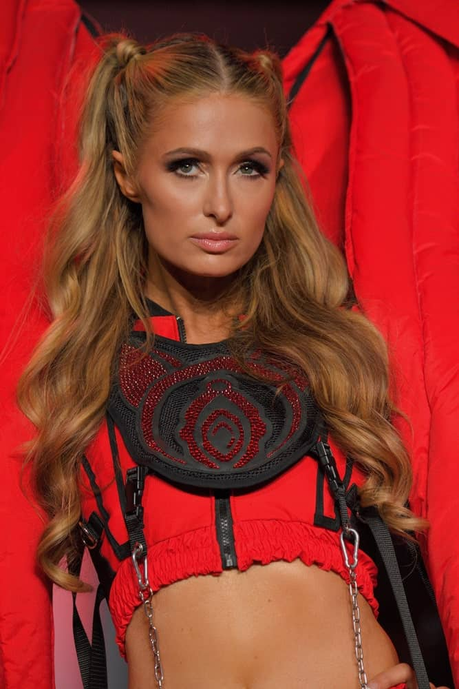 Paris Hilton slayed the runway for Namilia during New York Fashion Week: The Shows at Gallery II at Spring Studios on September 11, 2018 in an edgy red outfit. She finished the look with her waterfall waves center-parted and half tied on both sides.