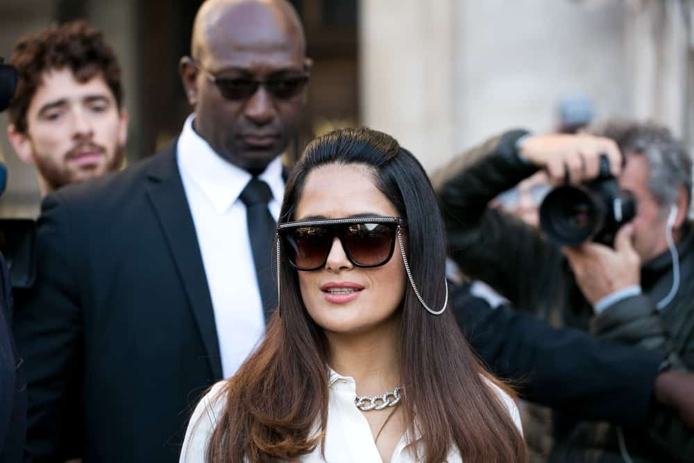 Salma Hayek was spotted last October 3, 2016, going to the Stella McCartney fashion show with her husband Francois-Henri Pinault. She was wearing a pair of fashion-forward sunglasses to complement her half-up loose and highlighted long hair.