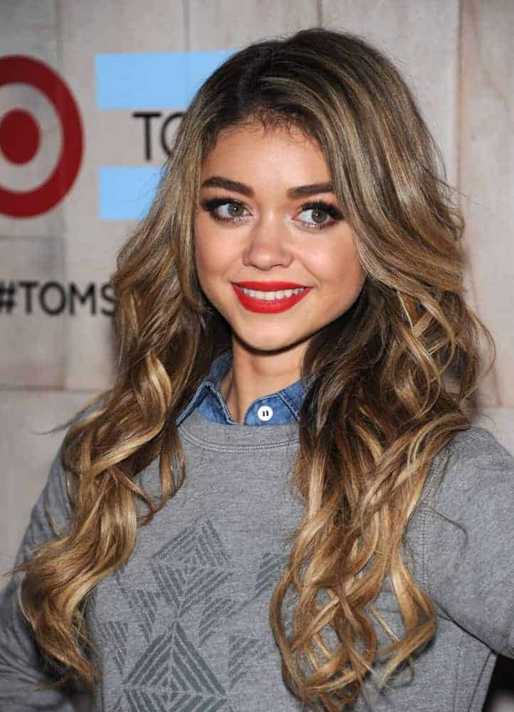 Sarah Hyland attended the TOMS for Target Partnership Celebration on November 12, 2014, in Culver City, CA. She was seen wearing a smart-casual outfit to pair with her long and wavy highlighted sandy blonde hairstyle with layers and slight tousle.