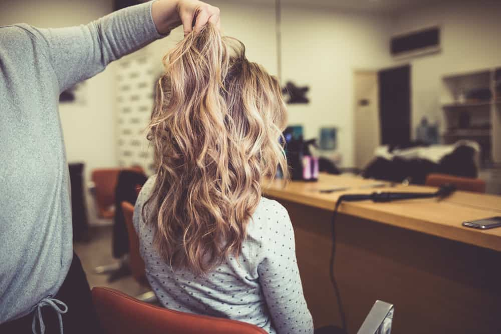 Woman getting balayage coloring technique done to hair.