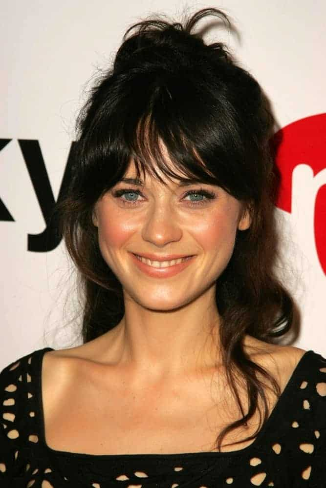 Zooey Deschanel was at the Lucky Magazine LA Shopping Guide Party on August 10, 2006, in Milk, West Hollywood, CA. She was charming in a black dress and messy tousled raven hairstyle with bangs and a bun.