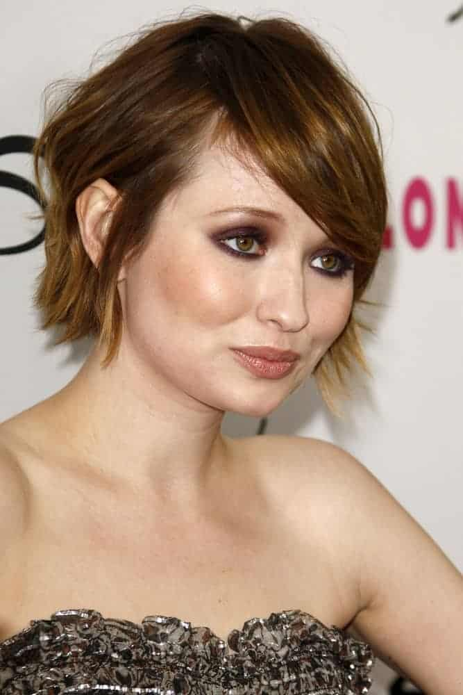Emily Browning was at the Nylon Magazine 12th Anniversary Issue Party at Tru Hollywood on March 24, 2011, in Los Angeles, CA. She paired her black strapless dress with a pixie highlighted brunette hairstyle that has long side-swept bangs.