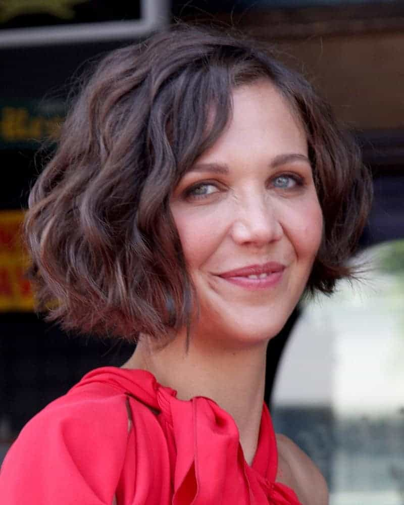 Maggie Gyllenhaal attended the Hollywood Walk of Fame Ceremony for Emma Thompson at Hollywood Walk of Fame on August 5, 2010 in Los Angeles, CA. She wore a charming red dress and paired with a shin-length curly brown hairstyle with a slight tousle.