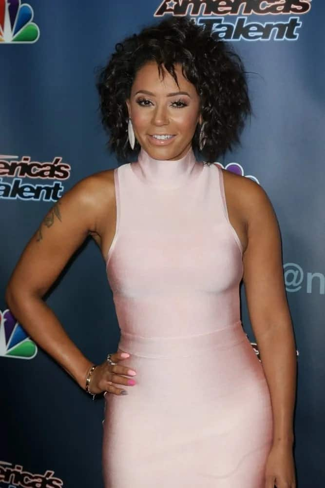 Mel B looks classy in a light pink slinky sleeveless dress, topping it off with a short naturally curly bob hairstyle as she attends the 'America's Got Talent' Season 10 Results Show on August 12, 2015.