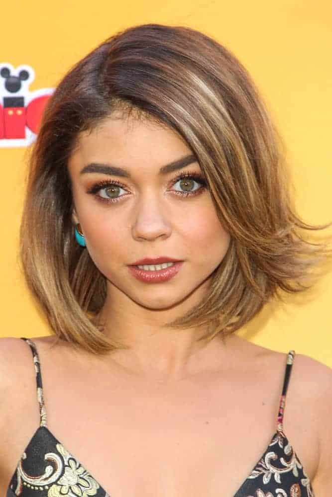 On November 14, 2015, Sarah Hyland attended the premiere of Disney Channel's 'The Lion Guard: Return Of The Roar' at Walt Disney Studios. She came wearing a simple black dress with a sandy blonde shoulder-length hairstyle with flippy bangs on one side.
