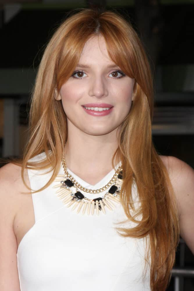 Bella Thorne with a center-parted hairstyle in Strawberry Blonde.