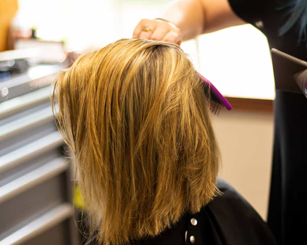 A long bob being layered for a stylish look.