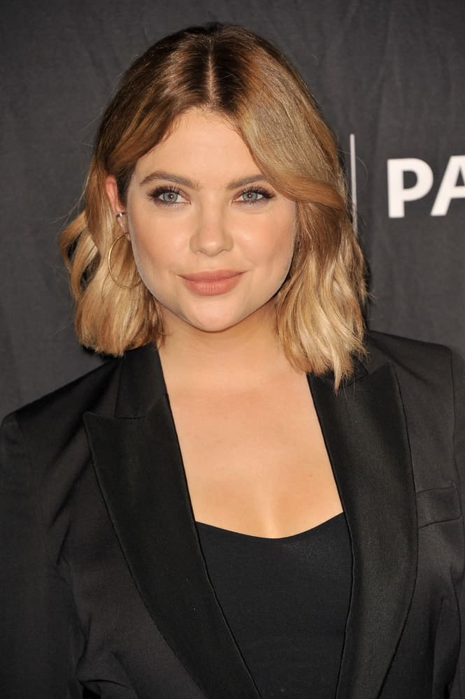 Light brown bob style haircut with a slight wave parted in the middle.