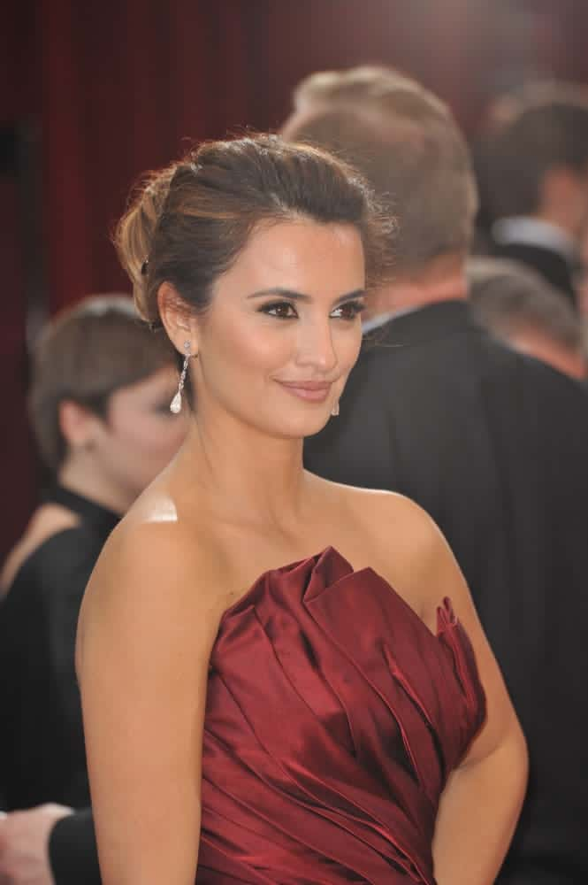 Penelope Cruz with a side-part pulled back hair into a bun.