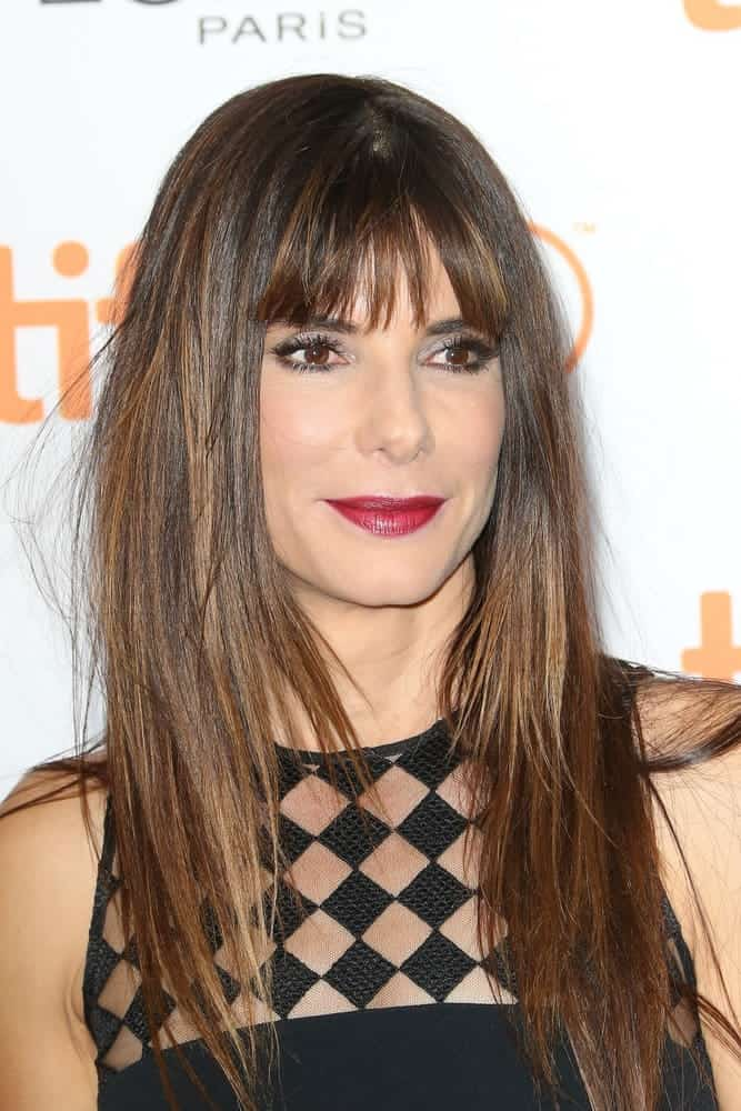 Sandra Bullock with long straight light brown hair with bangs.