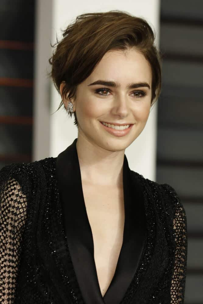 Lily Collins in a fresh and short haircut, swept to one side.