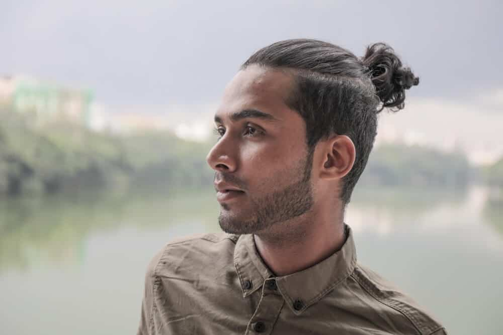 Side profile of a guy in a man bun.