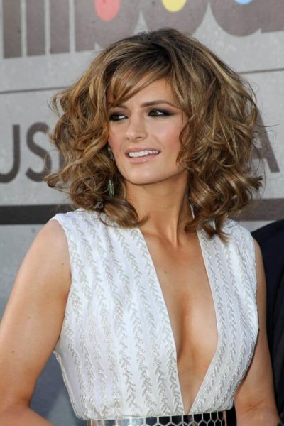 Stana Katic exhibiting her voluminous curls paired with side bangs