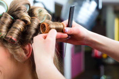stylist putting in hair rollers in woman's hair.
