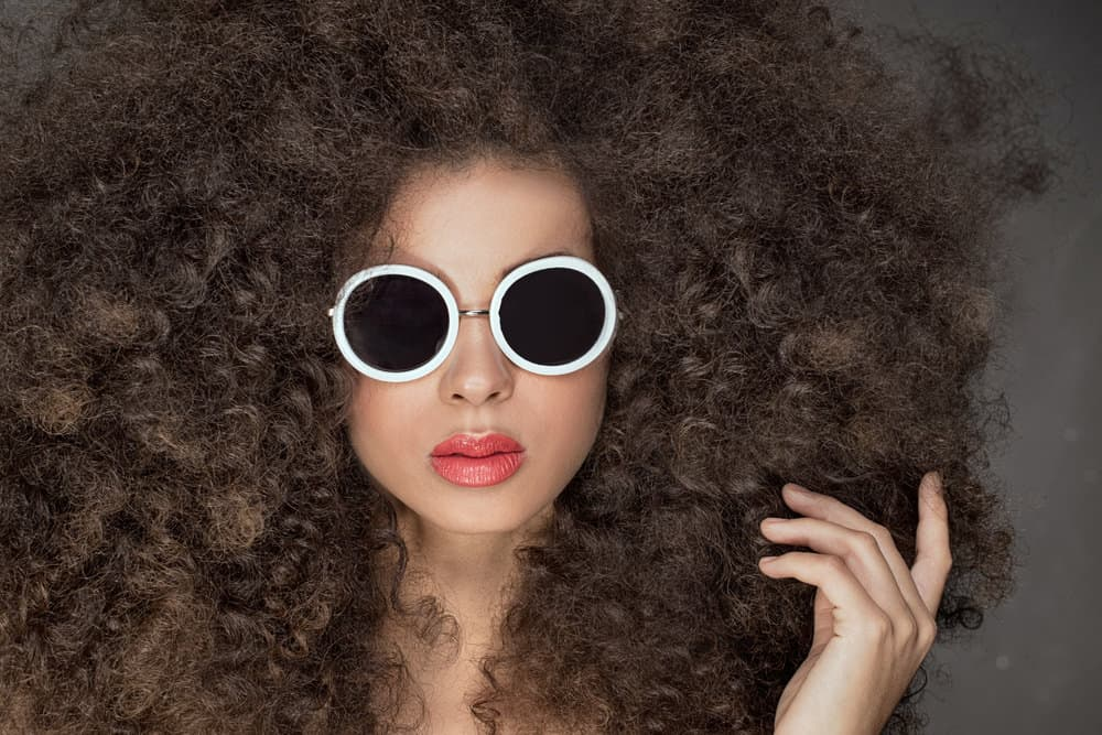 Woman with very curly hair and white sunglasses