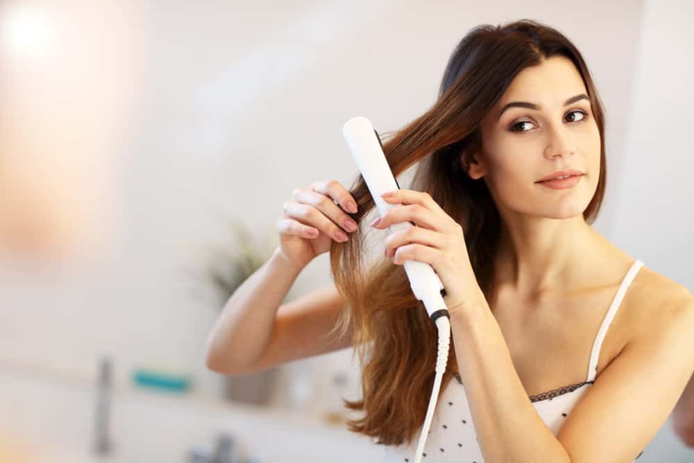 young woman with hair straightener flat iron