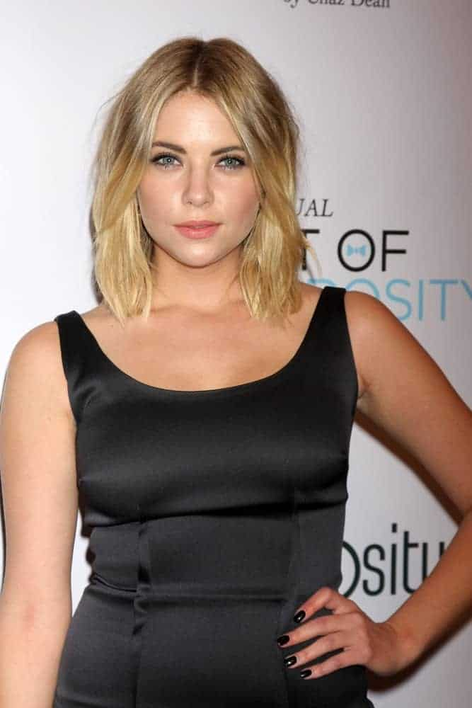 Ashley Benson wore a black dress at the 6th Annual Night Of Generosity at the Beverly Wilshire Hotel on December 5, 2014, in Beverly Hills, CA. She paired this with a shoulder-length wavy layered blonde hairstyle with highlights.