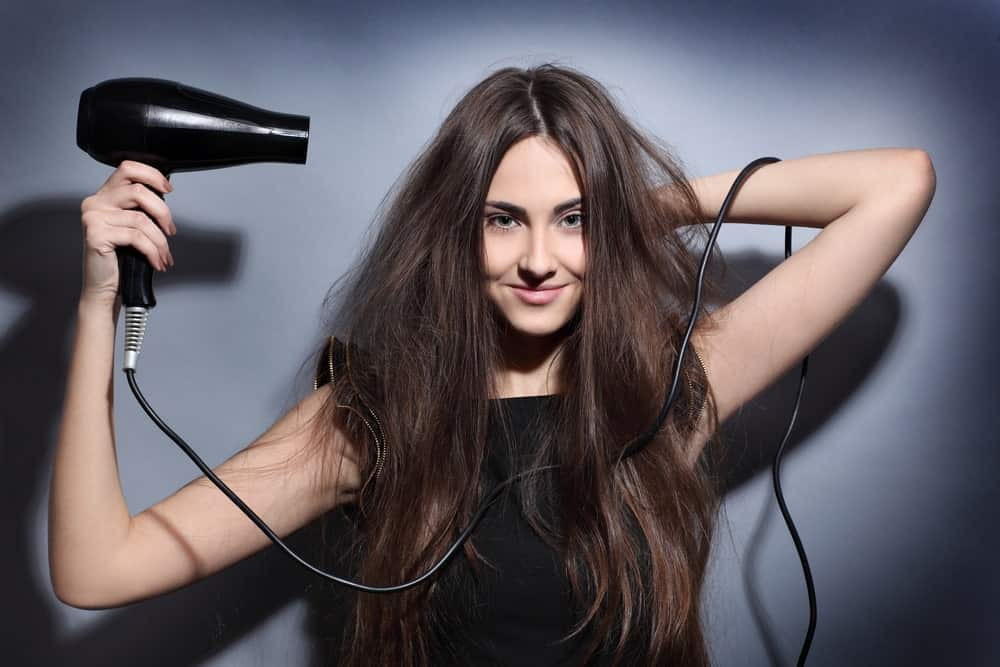 Gorgeous woman blow drying her hair.