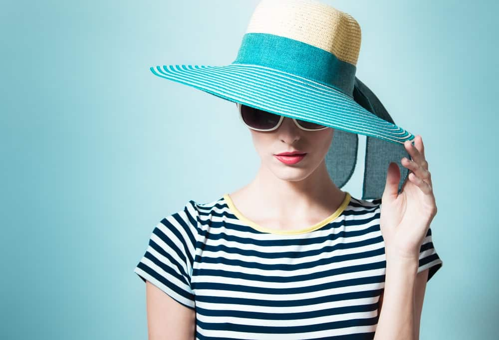Woman in stripe wearing a green sun hat.