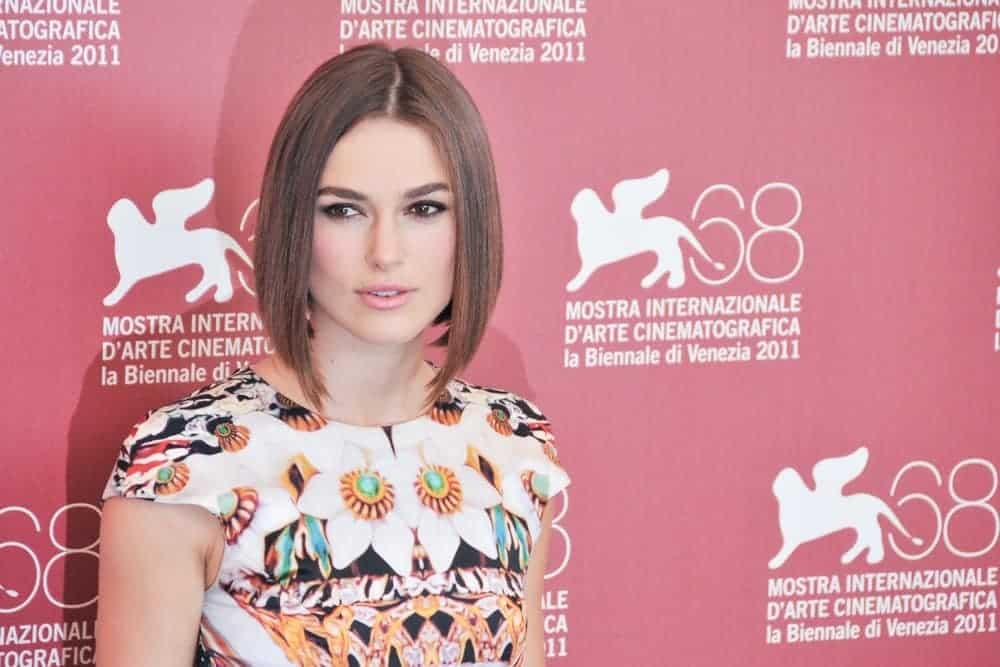 Keira Knightley poses at the photocall during the 68th Venice Film Festival at Palazzo del Cinema on September 2, 2011, in Venice, Italy. She wore a colorful floral dress with her straight bob hairstyle with a brown tone.