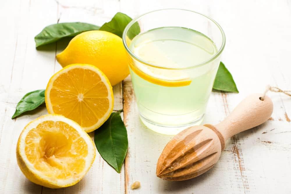 Lemon juice on a glasses with fresh lemons on the side.