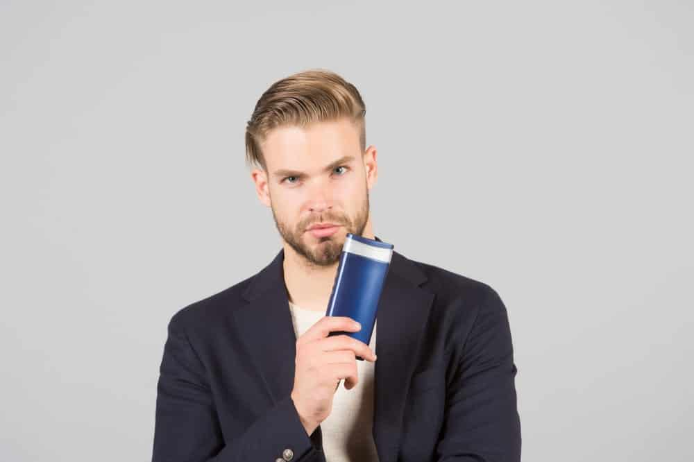 Man with a slick hairstyle holding an anti-dandruff shampoo.