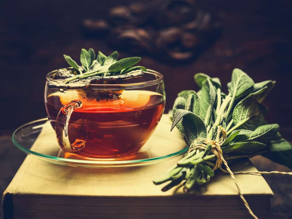 Sage extract on a cup along with its leaves.