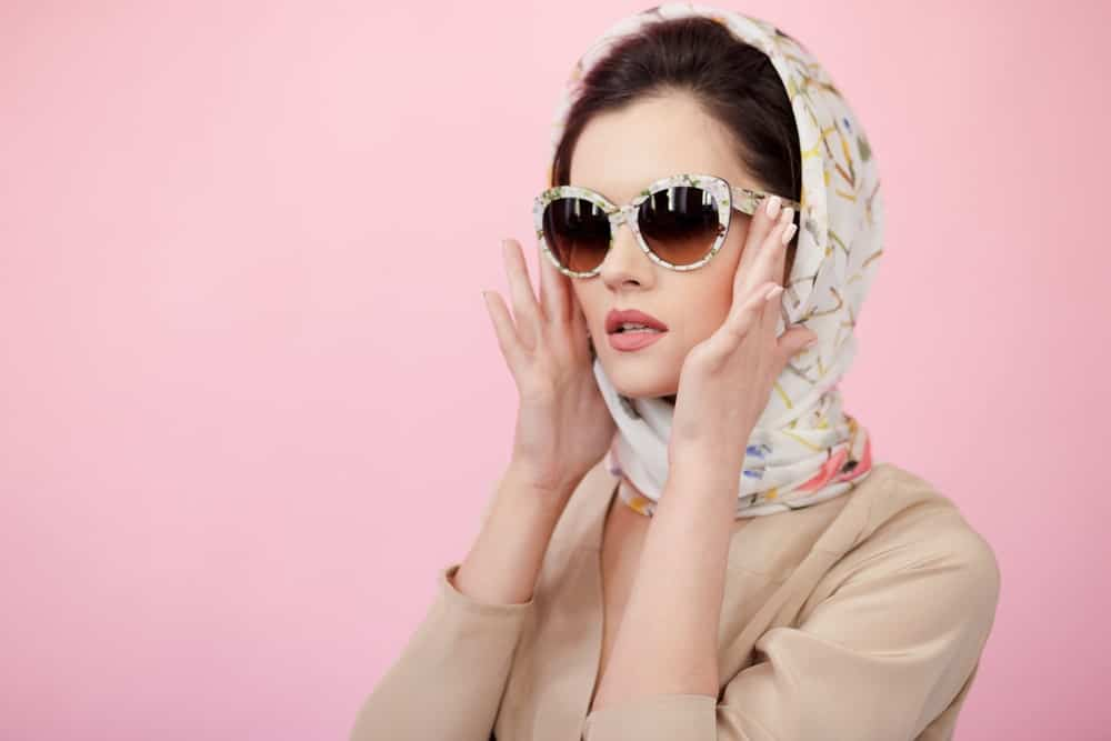 woman in a sunglasses wearing a scarf.